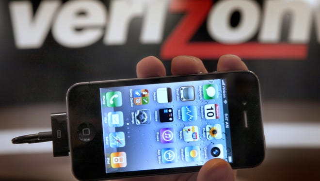 In this  file photo, a Verizon store manager holds up an Apple iPhone 4G.