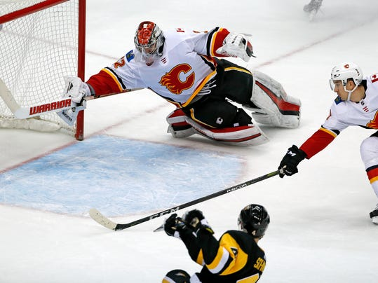 Pittsburgh Penguins' Justin Schultz (4) makes the winning goal in the overtime period of an NHL hockey game past Calgary Flames goaltender Jon Gillies (32) with Mikael Backlund (11) defending in Pittsburgh, Monday, March 5, 2018. (AP Photo/Gene J. Puskar)