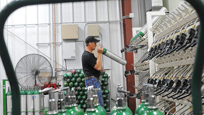 Aaron Dale, a fill plant technician at A-OX Welding Supply, preps medical oxygen tanks before filling them Monday, Sept. 14, 2015, in the fill plant at A-OX Welding Supply in Sioux Falls.