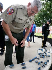 Rutherford County Sheriff Michael Fitzhugh, on Monday, Sept. 11, 2017, looks over the rocks painted for the Police Officers killed during the 9-11 attacks 16 years ago today. Fitzhugh picked up a rock with the name of Sergeant Rodney C. Gillis,  on it, who was killed as he attempted to rescue victims trapped in the World Trade Center after the Sept. 11th attack.