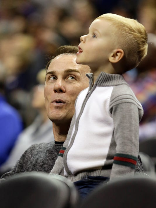Kevin Harvick, the 2014 NASCAR Sprint Cup Champion, watches the Oklahoma City Thunder battle the Charlotte Hornets with his son during the first half of an NBA basketball game in Charlotte, N.C., Saturday, Jan. 2, 2016. (AP Photo/Bob Leverone)