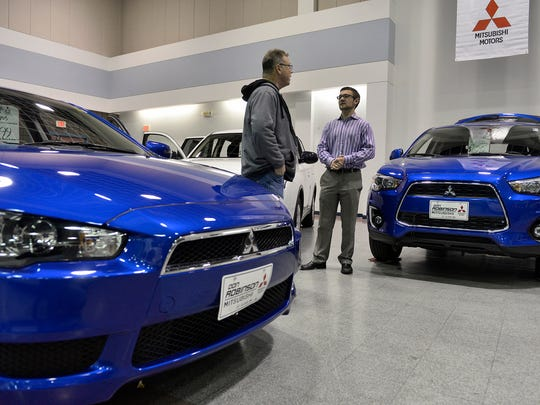 Chad Robinson, right, of Don Robinson Mitsubishi, talks to a potential customer Saturday about all wheel drive during the Central Minnesota New Car Show. Robinson is the son of owner Don Robinson.