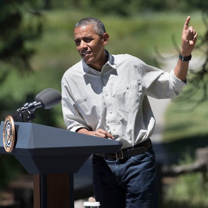 President Barack Obama gestures to Yosemite Falls while