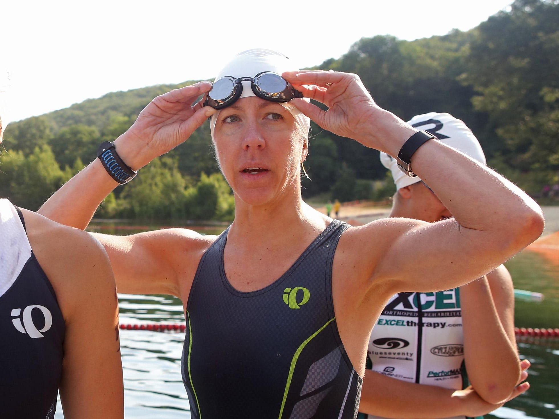 Paula Elejalde, 44, surveys Randolph Lake before starting the annual triathlon. Elejalde finished first in her hometown triathlon.