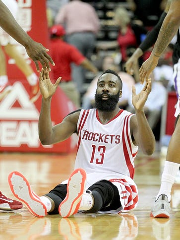 Houston Rockets guard James Harden is helped up by