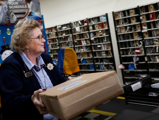 Postal worker Marion Smith brings packages to the counter