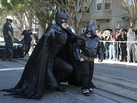 Miles Scott, dressed as Batkid, right, walks with Batman