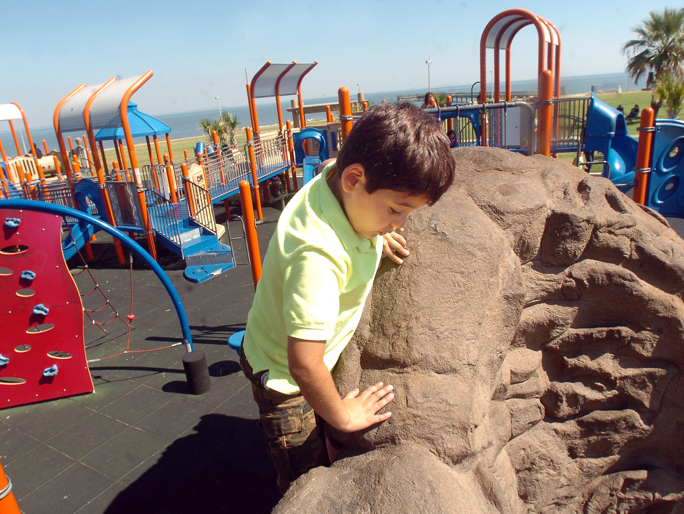 Andres Reyna, 8, climbs a rock-wall at Kids Place in