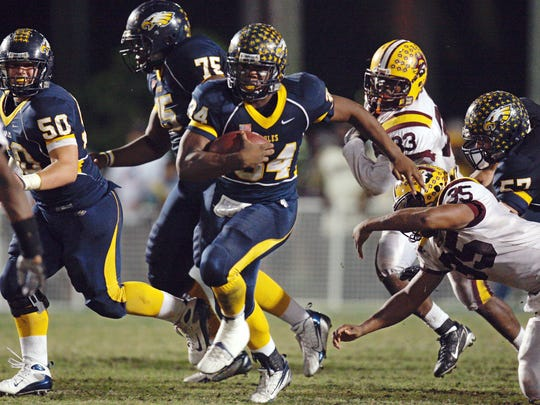 Naples' Carlos Hyde (34) breaks into Glades Central's secondary during the third quarter as Naples faced Belle Glade-Glades Central in the Class 3A Regional Final football game at Staver Field on Nov. 30, 2007. Naples advanced to the state semifinals, winning 27-24.