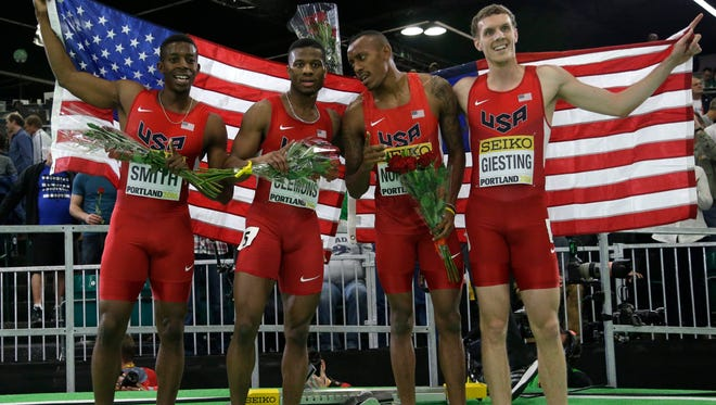 Members of the United States' 4x400-meter relay team (from left) Calvin Smith, Kyle Clemons, Vernon Norwood, and Christopher Giesting hold a flag and flowers as they celebrate winning the men's 4x400-meter relay final during the World Indoor Athletics Championships, Sunday, March 20, 2016, in Portland.