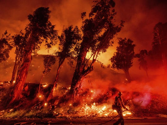 FILE - In this Nov. 1, 2019, file photo, flames from a backfire consume a hillside as firefighters battle the Maria Fire in Santa Paula, Calif. The decade that just ended was by far the hottest ever measured on Earth, capped off by the second-warmest year on record, NASA and the National Oceanic and Atmospheric Administration reported Wednesday, Jan. 15, 2020. (AP Photo/Noah Berger, File)