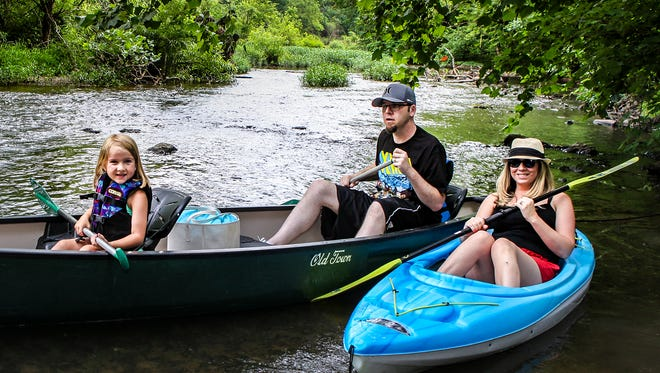 Anniston, Tabitha, Kenneth Swezea pose with Stones River Kayak boats near the Thompson Lane Greenway Trailhead in Murfreesboro.