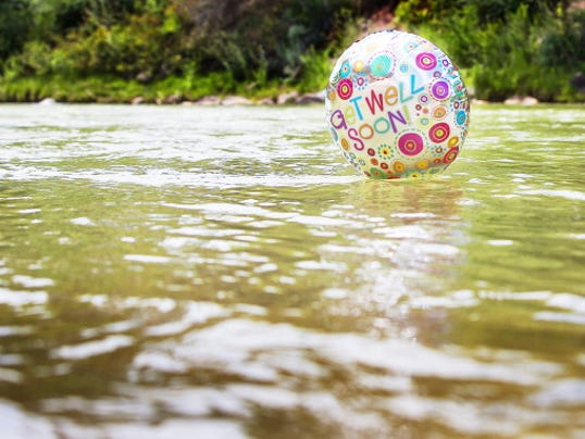 "A ""get well soon"" ballon floats in the contaminated waters of the Animas River flowing through Durango, Colo., Monday, Aug. 10, 2015.  (Shaun Stanley/The Durango Herald via AP)"