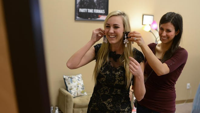 Jennie Collins, Miss Green Bay Area 2015, tries on earrings at Roxanne's Runway in Allouez while searching for something to wear for the talent portion of the Miss Wisconsin competition. She was accompanied by friend Candace Zilisch.