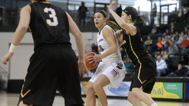 Green Bay Phoenix forward Mehryn Kraker looks for an open teammate while being defended by Michigan Tech guard Brenna Heise (right) in the second half. The Green Bay Phoenix defeated the Michigan Tech Huskies 74-50 at the Kress Events Center in Green Bay, Wis. on Saturday, Nov. 1, 2014.