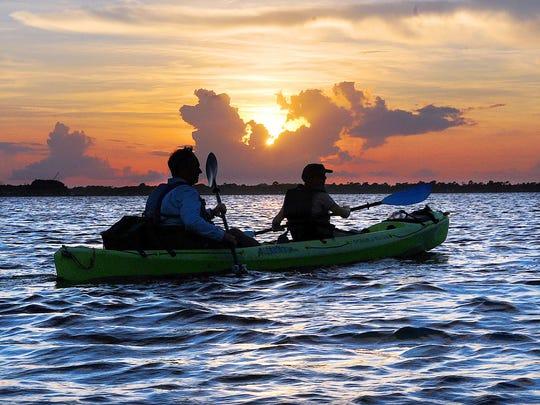 Kayakers enjoy the sun setting on the Banana River.