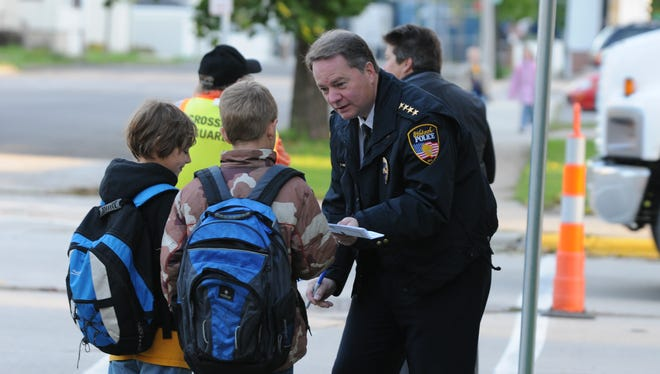 Oshkosh Police Chief Scott Greuel signs autographs Oct. 7, 2009, for Jefferson Elementary students during the National Walk to School Day.