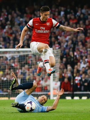 Arsenal's Olivier Giroud, top, leaps over Manchester City's Martin Demichelis during the English Premier League soccer match at the Emirates stadium in London.