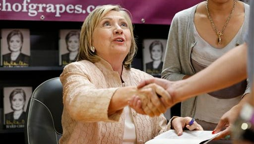 """Former Secretary of State Hillary Rodham Clinton speaks with customers at a signing for her book """"Hard Choices,"""" at Bunch of Grapes Bookstore on Aug. 13."""