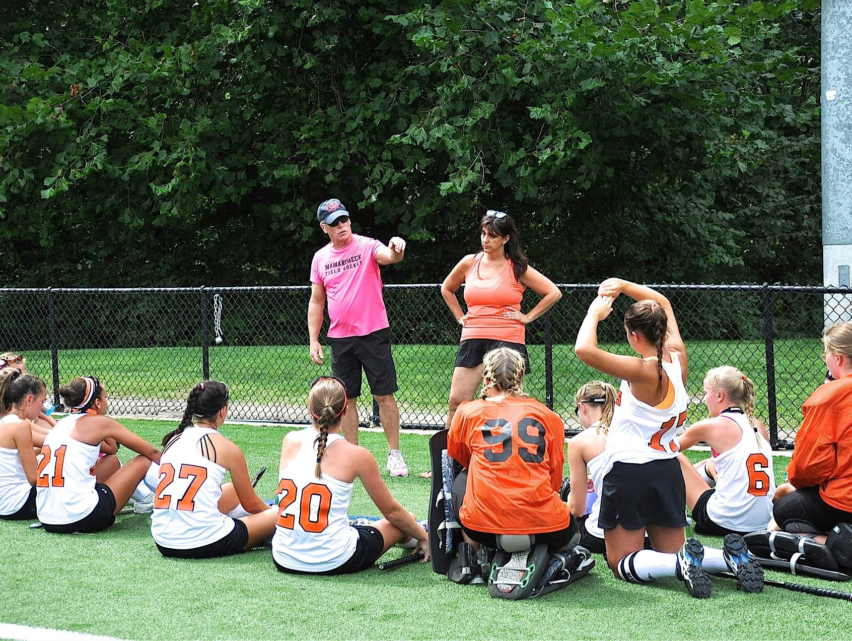 Head coach John Savaage and assistant Tricia Miller talk to their Mamaroneck Tigers during Saturday's New York/New Jersey Field Hockey Challenge that raised $1,200 in the fight against breast cancer.