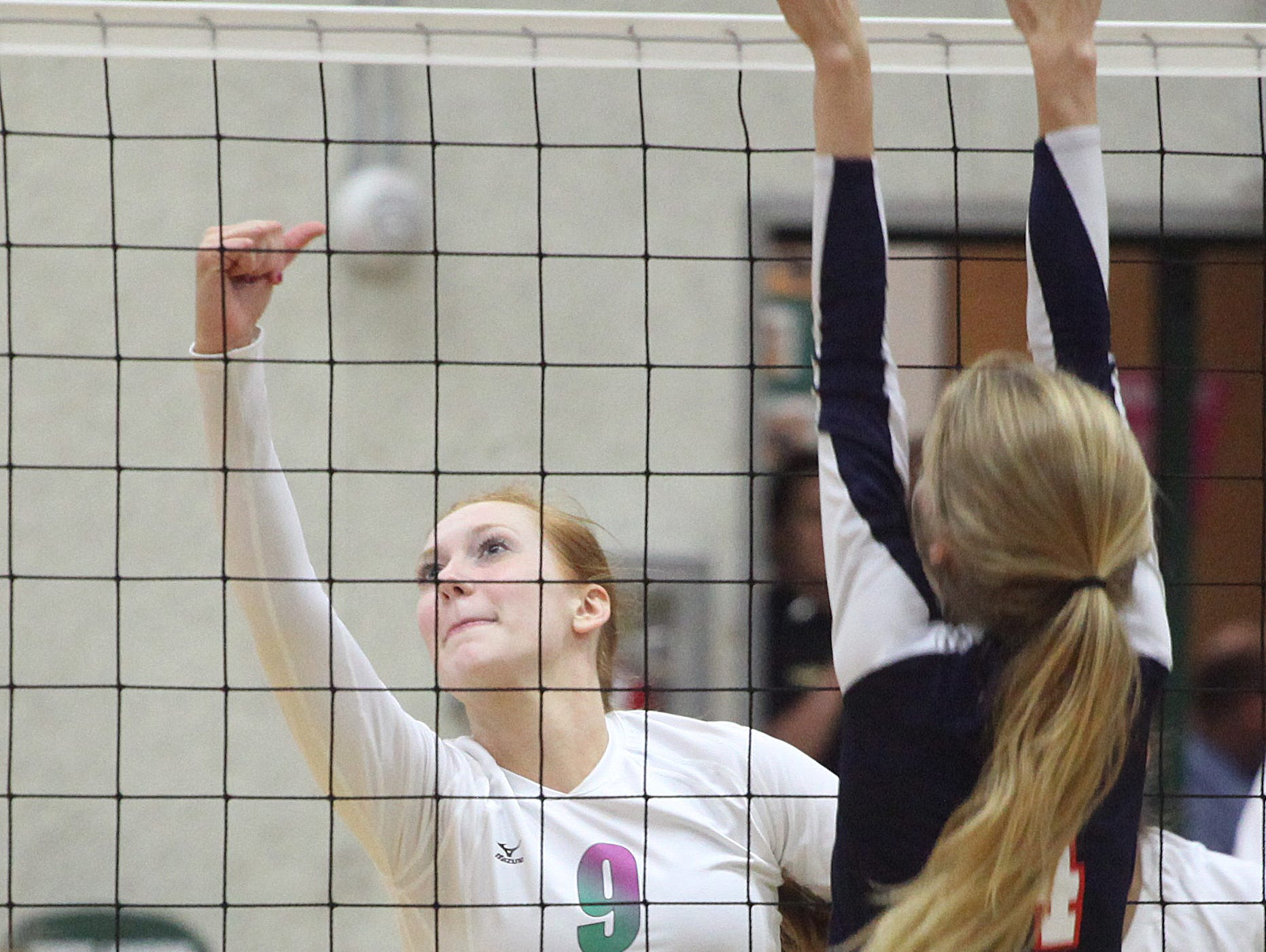 Fort Myers' Kaitlin Stewart spikes the ball past Estero's Brook Grimes during the 6A-11 volleyball final at Fort Myers High School on Thursday.