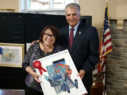 """Essex County Executive Joseph N. DiVincenzo Jr. congratulates Montclair resident Joyce Goldman, whose """"Flash"""" placed second in nonprofessional mixed media at the Annual Essex County Senior Citizens Juried Art Show."""