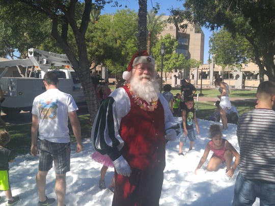 Glendale's Murphy Park is filled with tons of snow during the annual Christmas in July celebration.