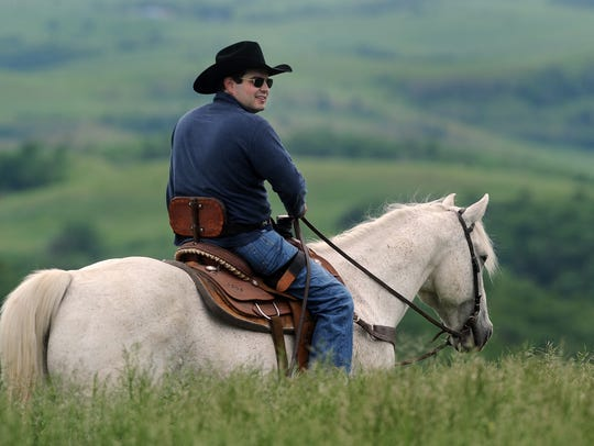 State Senator Billie Sutton rides horse on his family's