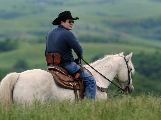 State Senator Billie Sutton rides horse on his family's