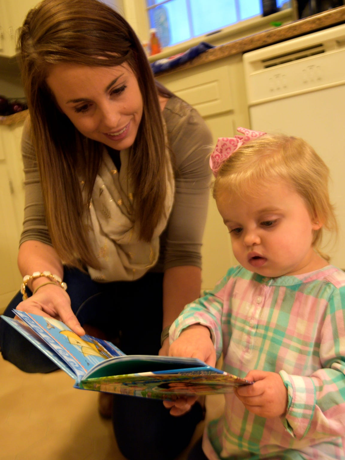 Maddy Keiper, 32, reads a book to her daughter, Kenleigh,