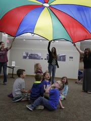 Children enjoy the parachute activity Monday, April 10, 2017, during story time at the Oshkosh Public Library as part of National Library Week.