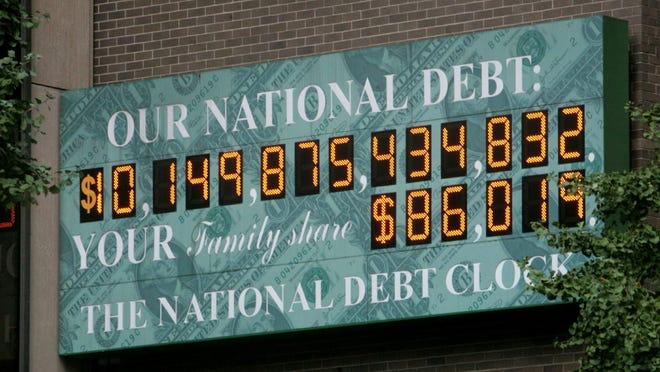 """Bebeto Matthews/APA clock near Times Square in New York City shows the national debt in 2008. The current amount of the U.S. national debt is shown on the National Debt Clock in New York, Thursday, Oct. 9, 2008. In a sign of the times, the National Debt Clock has run out of digits to record the growing figure. As a short-term fix, the digital dollar sign on the billboard-style clock near Times Square has been switched to a figure _ the """"1"""" in $10 trillion. It's marking the federal government's current debt at about $10.2 trillion. (AP Photos/Bebeto Matthews)"""