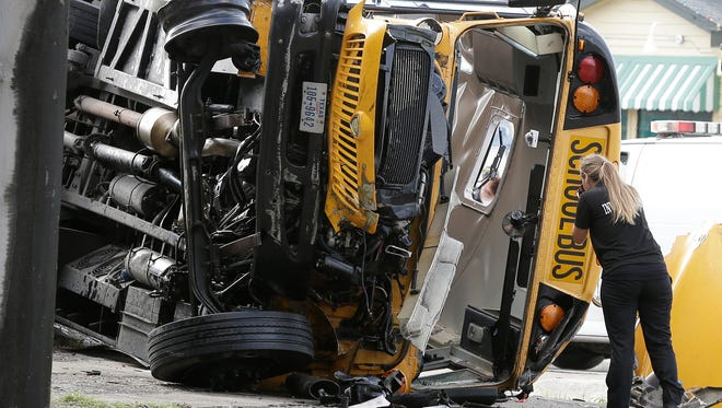 An investigator photographs the front of a Houston school bus after it drove off a highway overpass Tuesday, Sept. 15, 2015, in Houston. A female student died at the scene of the wreck and a second girl died at a hospital, according to a statement by the Houston Independent School District.  Three others seriously injured  (AP Photo/Pat Sullivan)