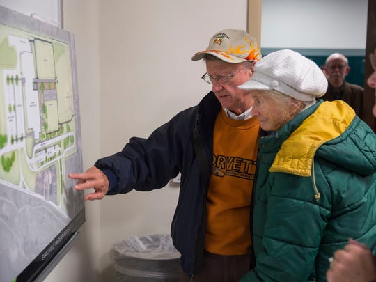 Bob Holder points out the map blueprint of the elementary school, that will start being built in February, to his wife, Linda Holder, at a recent EVSC school board meeting.