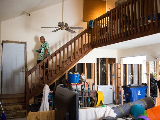 Rodney Malone navigates the interior of his home in Bonita Springs on Friday, Dec. 8, 2017, still visibly damaged from Hurricane Irma.