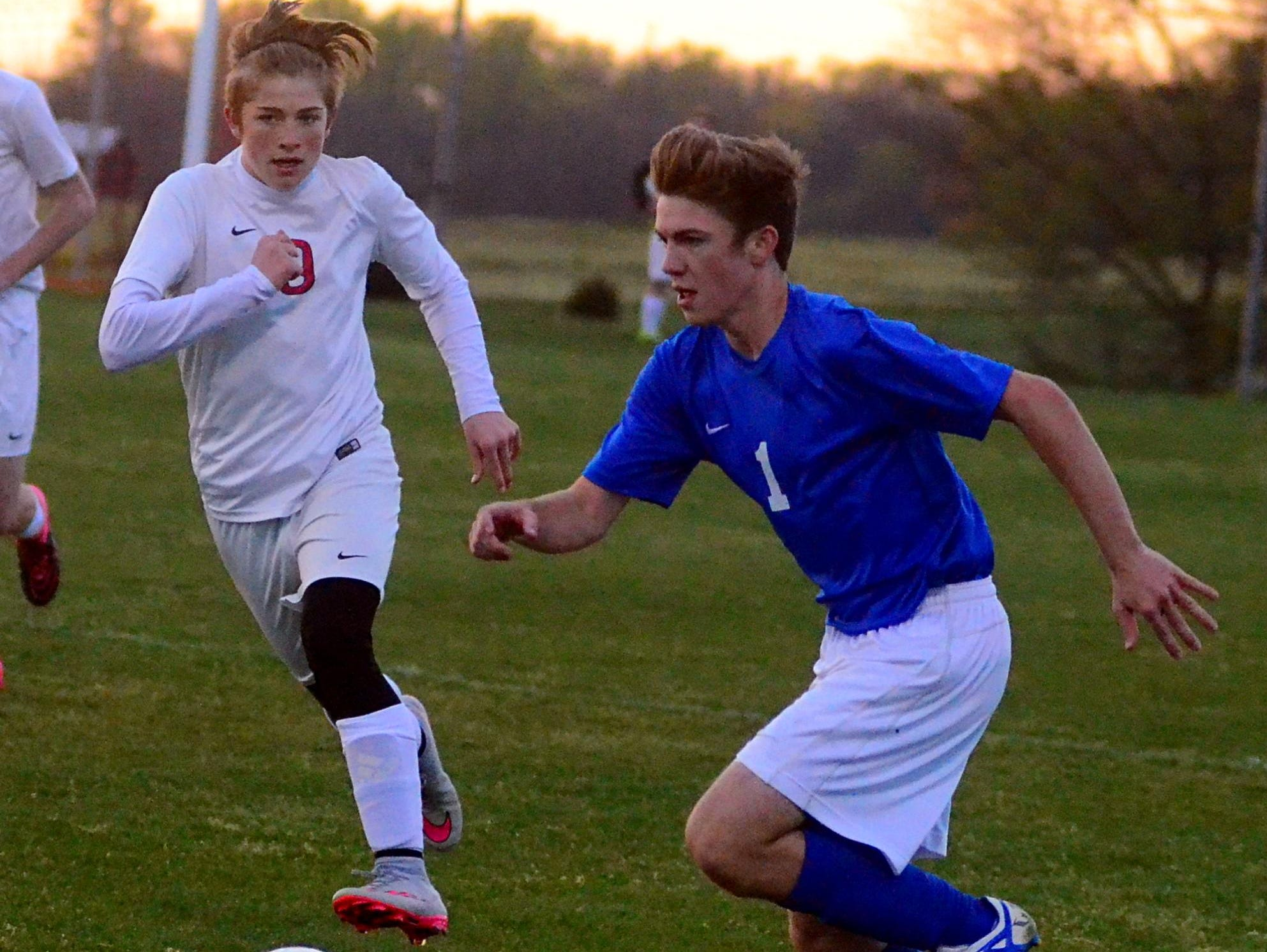 White House High sophomore Donovan Dixon dribbles upfield as White House Heritage sophomore Bronson Holloway pursues during first-half action.