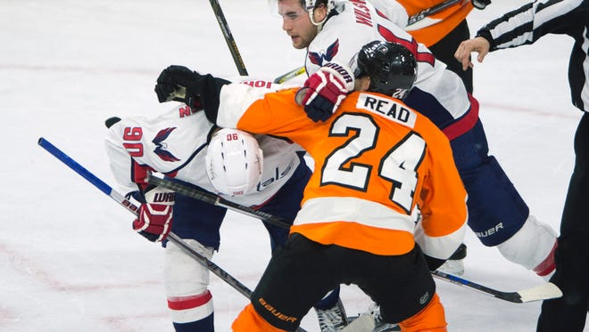 Flyers' Matt Read, front, battles Washington's Marcus Johansson, left, and Tom Wilson Wednesday night in Philadelphia. Flyers won 2-1.
