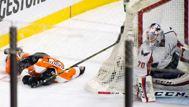 Flyers' Scott Laughton goes down after being checked Wednesday night in Philadelphia.