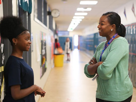 Kia Johnson, executive director of Great Oaks Charter School, is greeted by Syhirah Lewis, 13, as she visits various classrooms. Johnson is a recent graduate of the new leadership training program by Teach for America.