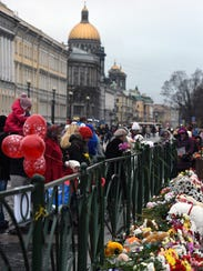 People stand next to flowers at a makeshift memorial
