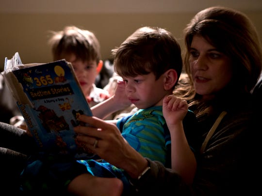 Leo and his younger brother, Hudson, curl up with their mom, Kristy, for a bedtime story on the couch. Leo loves books and often follows along by placing his finger under the words.