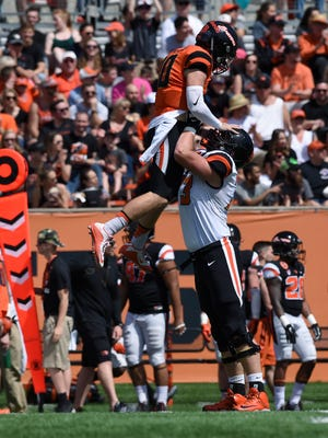Oregon State quarterback Darell Garretson (10) is hoisted by offensive lineman Blake Brandel (73) after throwing a 43-yard touchdown agains the defense during the Spring Game at Reser Stadium last Saturday.