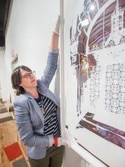 Director Amy Bowman-McElhone helps hang a work of art
