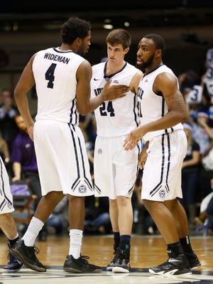 Butler's Tyler Wideman, left, Kellen Dunham, middle, and Roosevelt Jones celebrate a play against Northwestern in the second half of the game at Hinkle Fieldhouse Saturday December 6, 2014. Butler won 65-56.