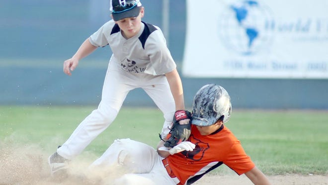 Rt. B Cafe's Braylon Banuet attempts to slide under the tag by Huebert Fiberboard shortstop Brad Norbury in the fourth inning Tuesday night in Cal Ripken Major at the COCOBA ballfield at Harley park.