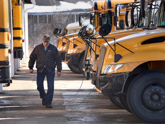 Don Beehler walks past a row of school buses at the