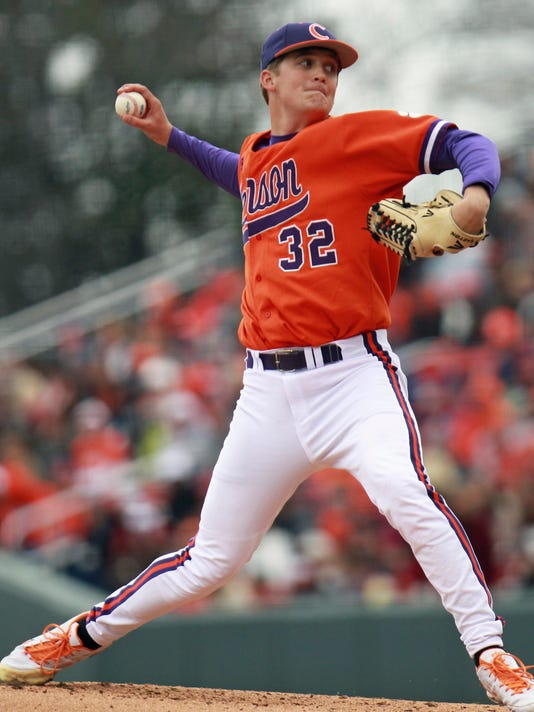 """FILE - In this March 2, 2013, file photo, Clemson's Clate Schmidt throws a pitch against South Carolina during an NCAA college baseball game in Greenville, S.C. As Dwight Schmidt absorbed the news of his younger son's baseball injury, he couldn't help but wonder, """"Why my boys?"""" It wasn't the first time he was faced with life-altering news about his sons. Two years ago, Clemson pitcher Clate Schmidt was diagnosed with nodular sclerosing Hodgkin's lymphoma. Fast forward to this year and Clate's younger brother Clark, a South Carolina righty projected as a potential first-round pick in the Major League Baseball draft, learned in the middle of his stellar junior season that he tore a ligament in his right elbow.(Mark Crammer /The Independent-Mail via AP, File)"""