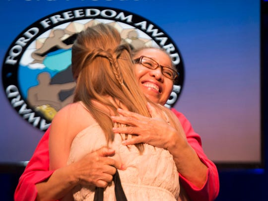 Ford Freedom Award essay contest finalist Mackenna Ozanich is welcomed onstage by Juanita Moore, president and CEO of the Charles H. Wright Museum of African American History, during the 16th Annual Ford Freedom Awards in Detroit in May 2014.