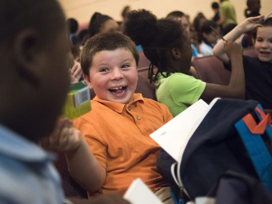 Joseph Schlender, 7, center, shows off his new school supplies to Jameer Miller, 7, left, during the giveaway at Freeman Elementary on Tuesday.