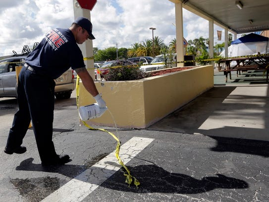 A Fort Myers fire fighter pours bleach over blood stains